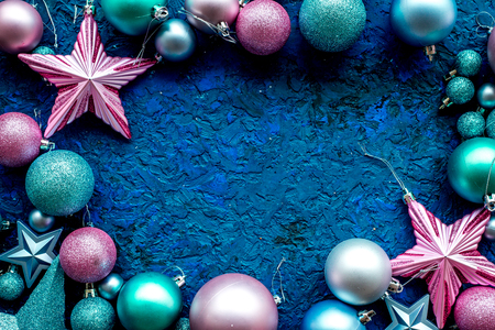 christmas tree decoration frame with balls and stars new year toys on blue background top view space for text