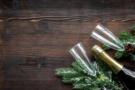 New Year 2018 celebration with spruce branch, champagne and glasses on dark wooden table background top view mock up