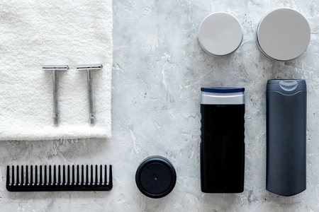 Mens shaving. Tools and cosmetics on grey stone background top view.