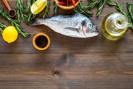 Mediterrane keuken. Dorado met rozemarijn, peper, Spaanse peper, citroen op houten hoogste mening als achtergrond.