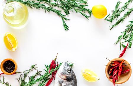 Preparing dorado with spices rosemary, chili, lemon. White background top view