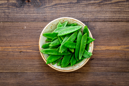 Fresh pea pods on the plate on dark wooden background top view.