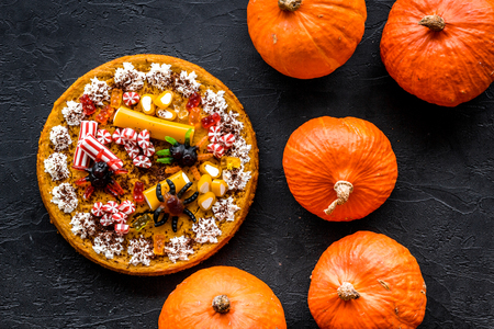 Homemade pie for halloween decorated gummy spiders among pumpkins on black background top view. Stock Photo