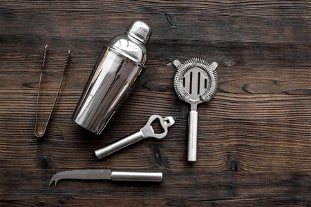 Instruments bartender. Shaker, strainer on wooden background top view.