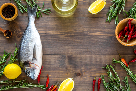 Mediterranian cuisine. Dorado with rosemary, pepper, chili, lemon on wooden background top view.