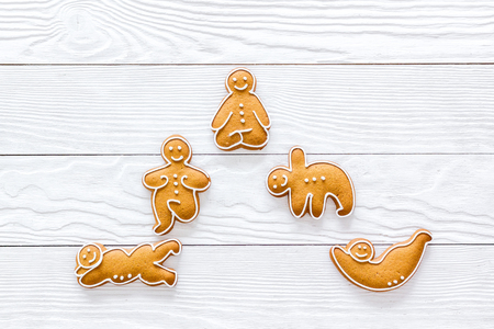 Gingerbread cookies in shape of yoga asanas on white wooden background top view.