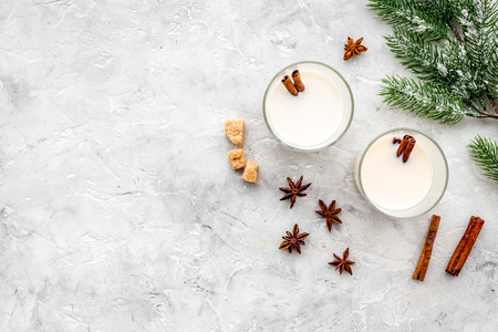 Celebrate new year winter evening with eggnog drink in glasses. vanilla, spruce branch and cinnamon . Stone desk background top view. Mock up Stock fotó
