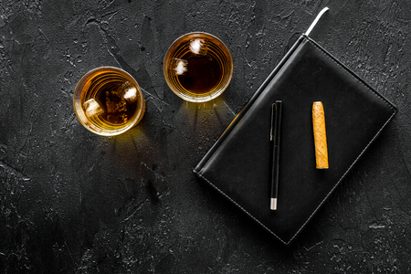 Man set. Whiskey with ice, cigar and notebook on black bar background top view Stock Photo