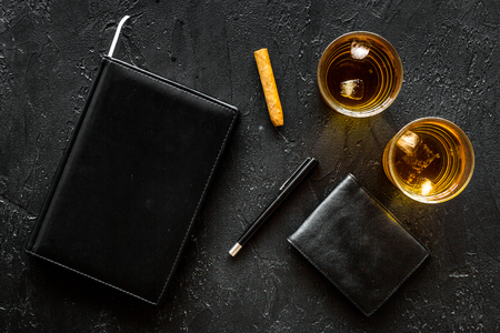 Man set. Whiskey with ice, cigar, wallet and notebook on black bar background top view copyspace