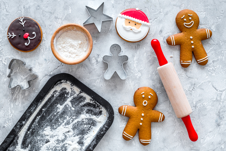 Cook gingerbread for new year 2018. Gingerbread man, rolling pin, flour on stone background top view mock up