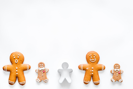 Gingerbread cookies of different shapes on white desk background top view space for text