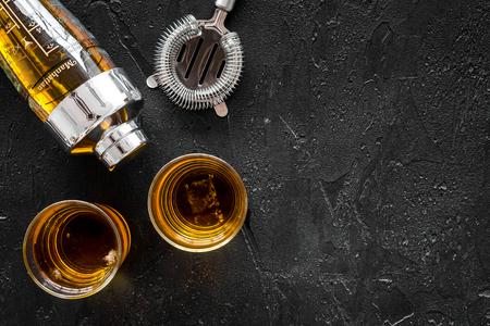 Barmen zet op de bar met whiskycocktails, schudbeker op zwarte achtergrond bovenaanzicht mock-up Stockfoto