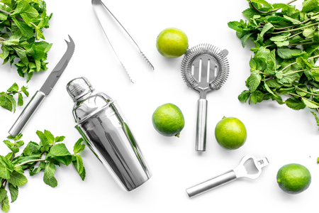 Make mojito cocktail with lime and peppermint in shaker. White background top view