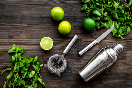 In the bar. Shake mojito. Lime, mint., barman tools on wooden background top view