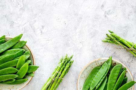 Healthy vegetarian food. Asparagus and pea on grey stone background top view. Stockfoto