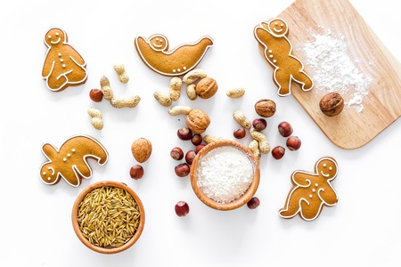 Healthy food for sportsman. Cookies in shape of yoga asanas near nuts on white background top view Stock Photo