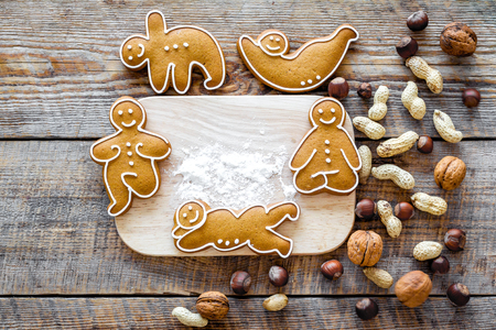 Healthy food for sportsman. Cookies in shape of yoga asanas near nuts on wooden desk background top view Stock Photo