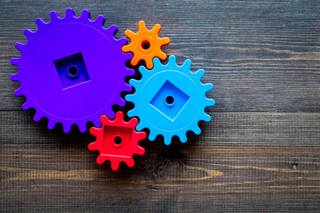 Bright gears for great technology of team work and correct mechanism on wooden table background top view copyspace Stock Photo