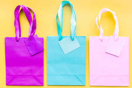 Colored paper shopping bags on yellow background top view.