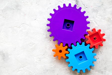 Colorful gears for ideal team work technology on stone table background top view mock-up