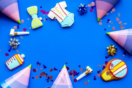 Cook gingerbread cookies with ticker tape for baby shower on blue colorful desk background top view mockup Stock Photo