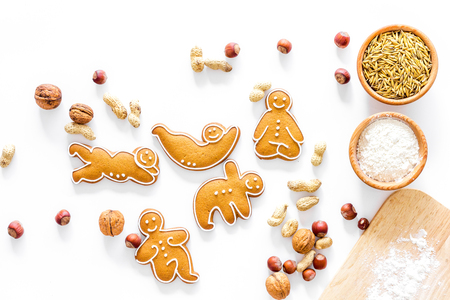 Healthy food for sportsman. Cookies in shape of yoga asanas near nuts on white background top view.
