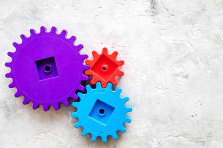 Moving forward concept, ideal operating principle with gears and wheels on stone desk background top view mock up Stock Photo