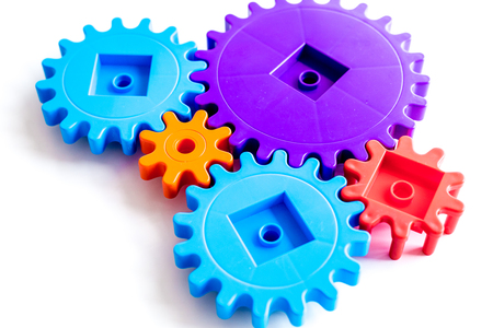 Moving forward concept, ideal operating principle with gears and wheels on white desk background