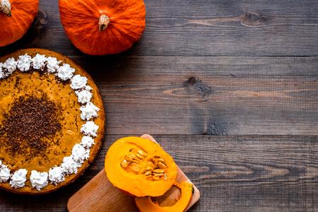 Pumpkin pie for thanksgiving day on dark wooden background top view.
