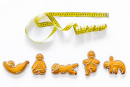 Sport for slimming. Yoga asanas cookies and measure tape on white background top view. Stock Photo