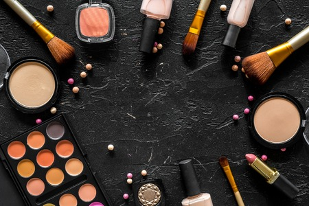 Bulk cosmetics beige and nude colors on black background top view copyspace