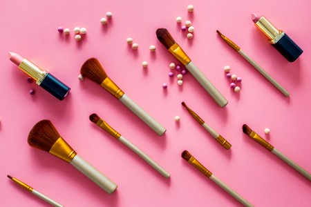 Natural makeup. Ball blushers and brushes pattern on pink background top view