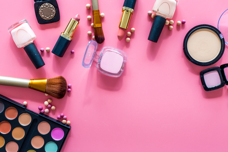 Decorative cosmetic set for natural makeup on pink background top view copyspace