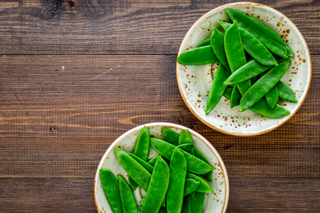 Fresh pea pods on the plate on dark wooden background top view copyspace