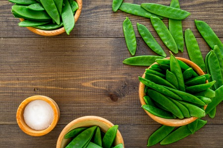 Fresh pea pods in bowls on dark wooden background top view copyspace Stock Photo