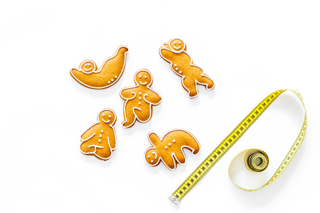 Sport for slimming concept. Yoga asanas cookies and measure tape on white background top view