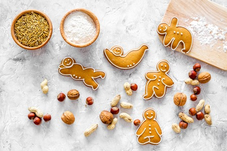 Healthy food for sportsman. Cookies in shape of yoga asanas near nuts on stone background top view