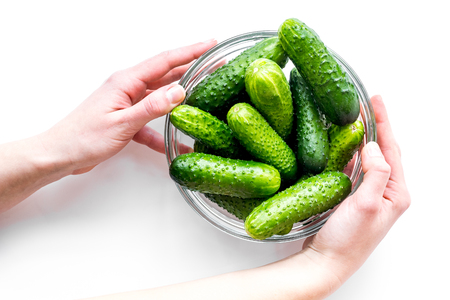 Hands take fresh cucumbers in bowl. White background top view copyspace Stock Photo