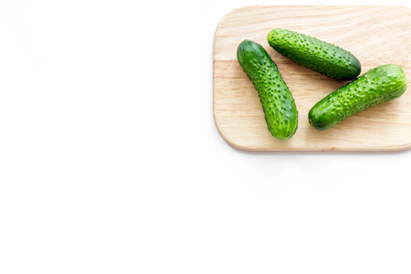 Make salad with fresh cucumbers. Vegetables on cutting board on white background top view copyspace