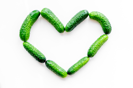 Fresh cucumbers in shape of heart on white background top view mockup Stock Photo