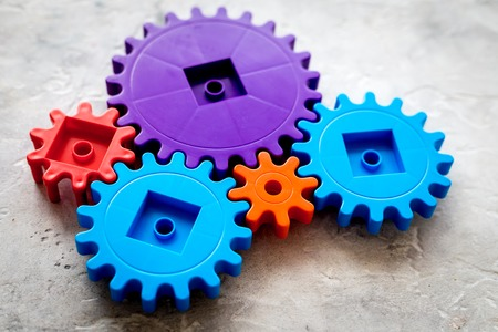 moving forward concept, ideal operating principle with gears and wheels on stone background Stock Photo