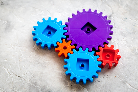 bright gears for great technology of team work and correct mechanism on stone background Stock Photo