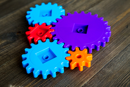 moving forward concept, ideal operating principle with gears and wheels on wooden background
