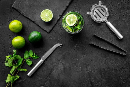 In the bar. Shake mojito. Lime, mint., barman tools on black background top view copyspace