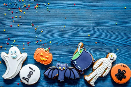 Cook halloween gingerbread cookies with witch, bat. Blue background top view copyspace