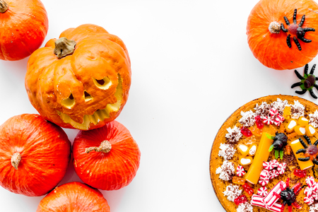 Halloween tradition. Pumpkin pie and pumpkin with scary face on white background top view copyspace