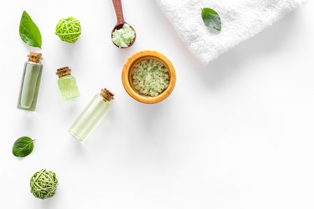 natural cosmetics with tea olive leaves and oil for homemade spa white table background top view mock up