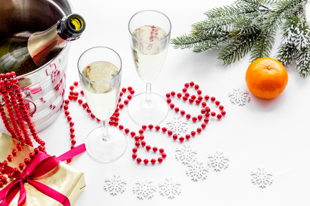 New Year 2018 background. Champagne in bucket, glasses with beverage, tangerines and decoration on white background