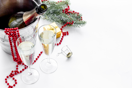 New Year 2018 background. Champagne in bucket, glasses with beverage, spruce branch and decoration on white background copyspace