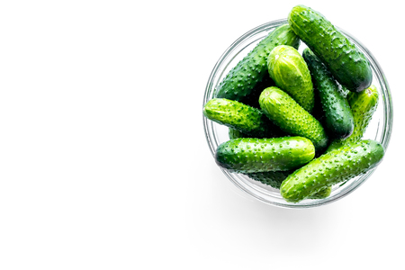 Fresh cucumbers in bowl on white background top view copyspace Stock Photo